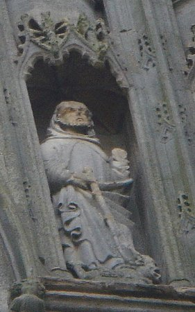 St. Guthlac holding the whip given to him by St. Bartholomew and, a demon at his feet. (The statue from the second tier of the Croyland Abbey's west front of the ruined nave; dates from the XVth century).